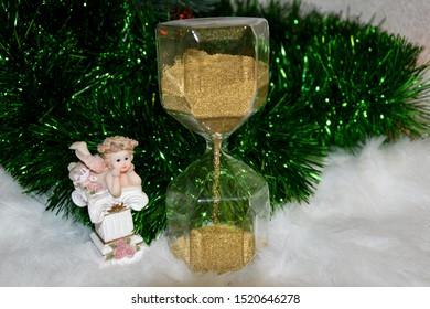 In the foreground is the figure of a guardian angel next to the hourglass, time is running out and the last minutes remain. The concept of time passes, everything changes, but the guardian angel is al
