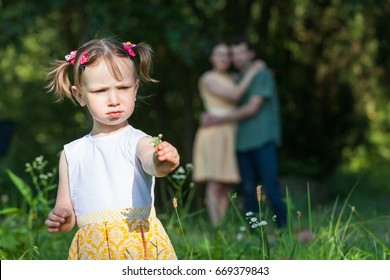 In foreground girl holding a flower. In background parents embracing each other looking at her. Photo.
