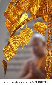 Foreground of golden leaves framing a blurred background image of a Buddhist monk praying.