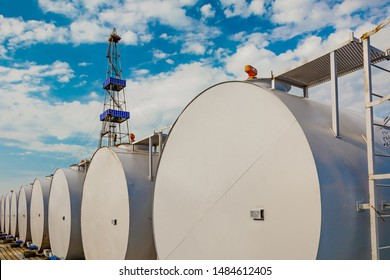 In the foreground are gray cylindrical tanks for storing oil and fuel reserves. Located horizontally in a row. In the background is a rig for drilling oil wells. Blue cloudy sky.