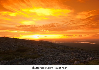 Foreground has rocks common for Finnish lapland mountains. Background has spectacular sunset.