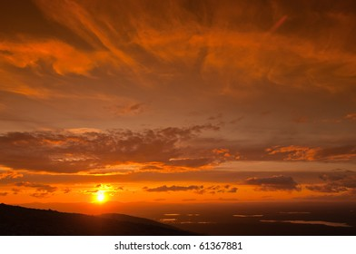Foreground has a silhouette of mountain. In the background many small lakes and orange sunset.