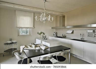 foreground the kitchen island with ancient chandelier on the bacground the white kitchen cabinets and steel hood, uner the wondow there is a  food trolley