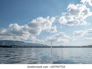 With a foreground of Lake Geneva, the iconic Jet d'eau soars high above Geneva's skyline under summer clouds streeking diagonally across a blue sky