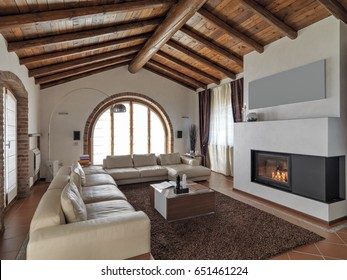 foreground of a leather couch and  fireplace in the modern living room with tiles flooring and wooden ceilings