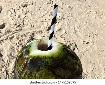 Foreground, natural coconut, with water, green bark. Inside straw, black and white. Rich in potassium. Background, beach sand.