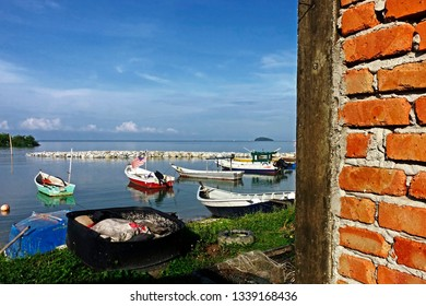 Foreground of old red brick wall and traditional fisherman sampan boats in Port Dickson beach Malaysia  July 30 2014