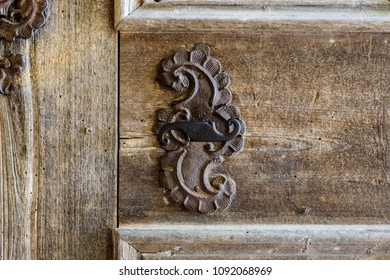 Foreground of old wooden door with iron handle. Old rusty gate handle on wooden door.