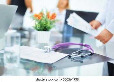 in the foreground of the photo stethoscope and medical card of the patient in the workplace. in the background the doctor-diagnostician, holding a card with the tests.