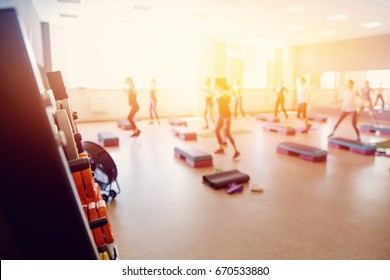 In foreground projectile disc for bar, in background group of girls of friends are engaged in fitness. Sports hall concept gym. Glare sun