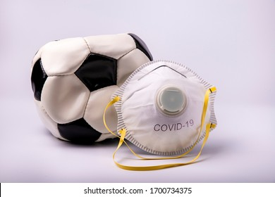 in the foreground a protective mask and a deflated soccer ball to symbolize the suspension of the soccer field in Italy and Europe as a preventive measure during the risk of coronavirus infection.