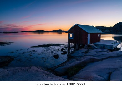In the foreground a red boathouse on the cliffs with wooden decks for boats. In the background a colorful sky and calm sea