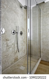 in the foreground the shower box with stone coating and stone shower tray while the access door is made of glass