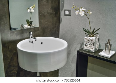 in the foreground the sink suspended in the modern bathroom with the orchid vase on the shelf,  near, the steel soap dispenser