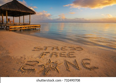 """Foreground written in the sand """"stress free zone"""" at sunset in Mauritius Island with Jetty on the left side."""