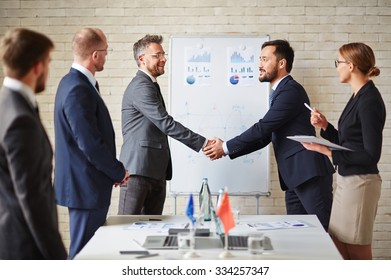 Foreign business partners greeting one another by handshaking