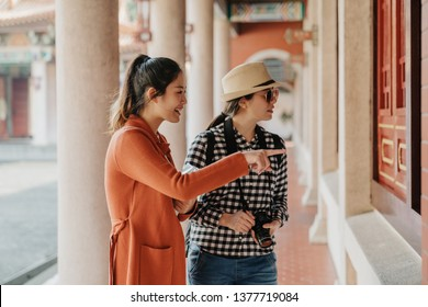foreign female visitors looking inside room of historic building. smiling smart girl points finger explains to friend in sunglasses. two asian women tourists sightseeing chinese temple beijing china