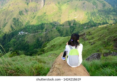 A foreign girl is sitting and looking the beautiful valley at the little Adams peak in Ella, Sri Lanka. Ella is a great location for viewing some of the best natural scenery in Sri Lanka