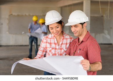 foreign Investor talking salesperson about the construction project with blurred engineers consulting in behind