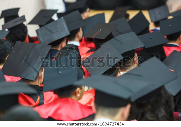 Foreign medical students in square academic graduation caps and black raincoats during commencement