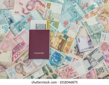 Foreign passport with boarding pass  on Asian money background . Currency of Hong Kong, Indonesia, Malaysia, China, Thai, Singapore dollar. Travel and business concept