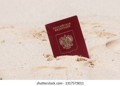 Foreign passport of Russian Federation put into the sand on the beach symbolizing travelling to tropical destinations