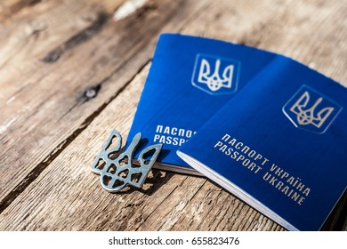 The foreign passport of Ukraine. The flag and the emblem are a symbol of the country. On a wooden background.