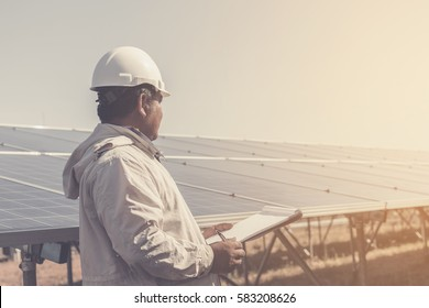 foreman checking job routine of labor working on cleaning solar panel at outside ; operation working on preventive and maintenance in solar power plant for great efficiency