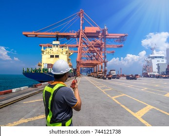 Foreman at container terminal is controlling for cargo operation at port.