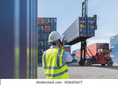 Foreman control loading Containers box from Cargo freight ship for import export.Thailand construction worker or supervisor or architect with clipboard on a building site in Asia