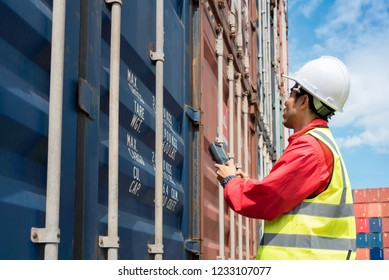 Foreman control loading Containers box from Cargo freight ship in Warehouse shipping transportation concept.