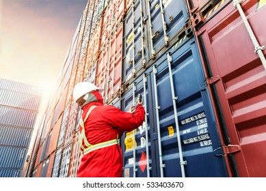 Foreman control loading Containers box from Cargo freight ship for import export.