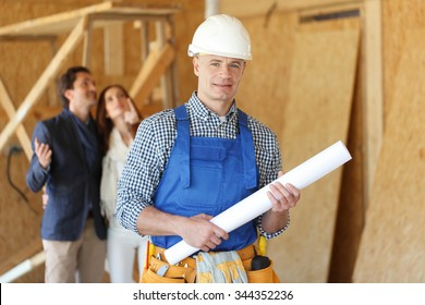 Foreman with design plans and young couple looking at new house