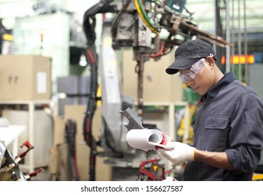 Foreman in a factory checking quality of work