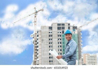 Foreman in hardhat reading blueprints on building site