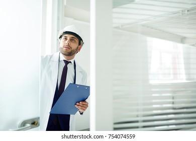 Foreman in helmet and whitecoat opening door of office in new building