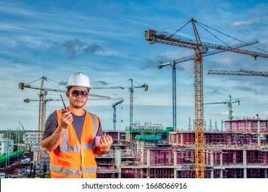 Foreman holding blueprint for control working by radio communication at high building construction site
