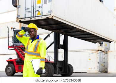 Foreman on Forklifts in the Industrial Container Cargo freight ship. Foreman is tired from working in hot weather. Foreman using laptop computer in the port of loading goods.
