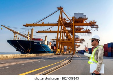 Foreman with radio communication in action for working at container loading in a cargo freight ship with crane to shore lift up loading. import and export logistic and transportation concept.