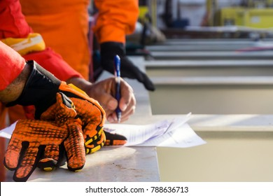 A foreman reviews and put a signature to a safety checklist prior to heavy lifting activity on a construction barge at oil field