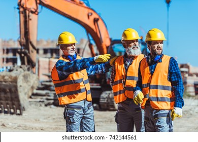 Foreman showing builders something at the construction site by pointing his hand