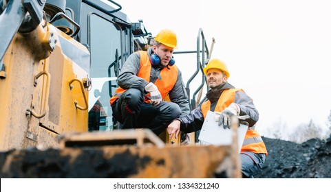 Foreman showing worker in open-cast mining pit direction with arm stretched