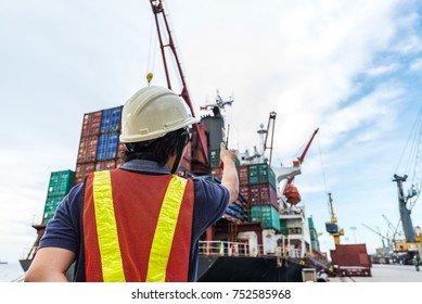 foreman stevedore working in yard terminal of the port checking safety equipments readiness for start loading cargo anytime