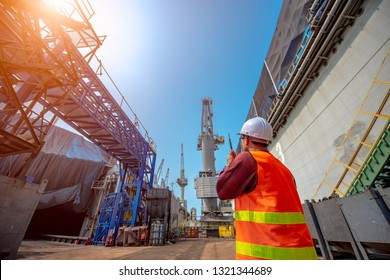 foreman, supervisor, port controller, loading master in charge of working in the dock at workplace, control and communication to the teamwork by walkie talkie radio for job done in the same direction
