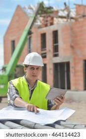 Foreman using digital tablet on construction site, France