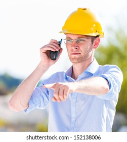 foreman with walkie talkie pointing at something
