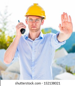foreman with walkie talkie showing forbidding gesture of stop