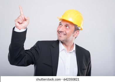 Foreman wearing hardhat pointing up and smiling on grey background