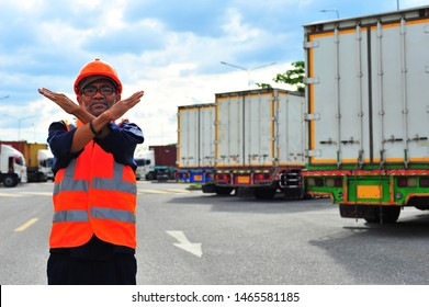 Foreman wearing safety helmet with safety vest making stop with hand at parking lot because it is prohibited to enter unless the employee