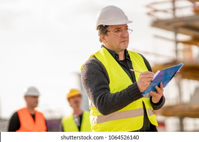 Foreman at work on construction site checking his notes and drawing plan on clipboard